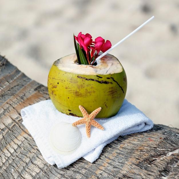Кокосовый коктейль с соломинкой на пальме на пляже Бесплатные Фотографии