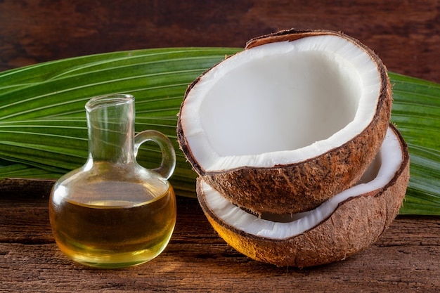 Coconut and coconut oil on wood background. Premium Photo
