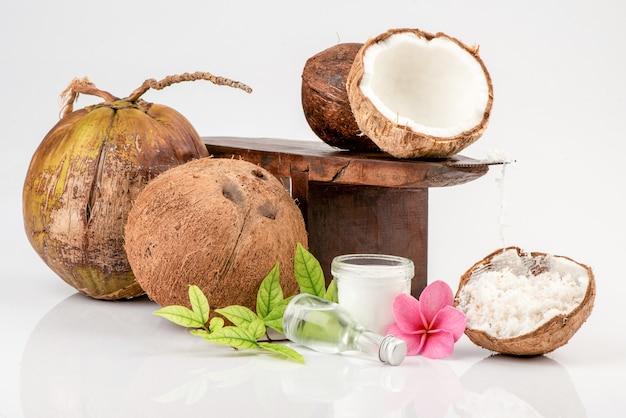 Кокосовая терка, измельченный кокос, весь кокос, половина кокоса и масло в стеклянной бутылке, изолированной на белом. Premium Фотографии