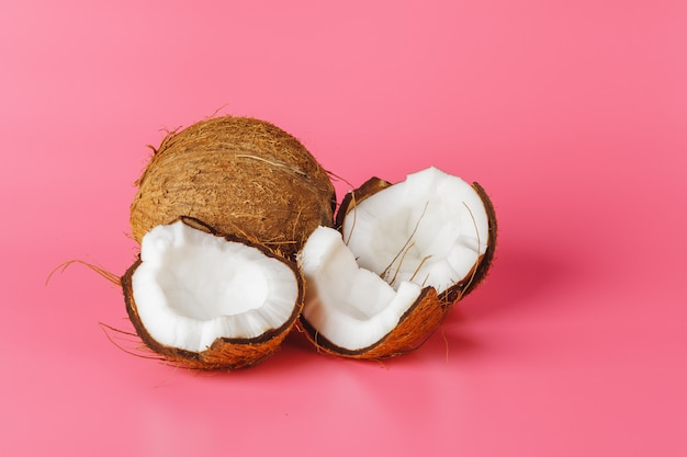 Coconut halves on a bright pink Premium Photo