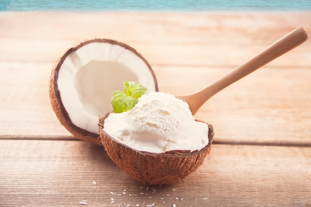 Coconut ice cream on the wooden table with mint leaf Premium Photo