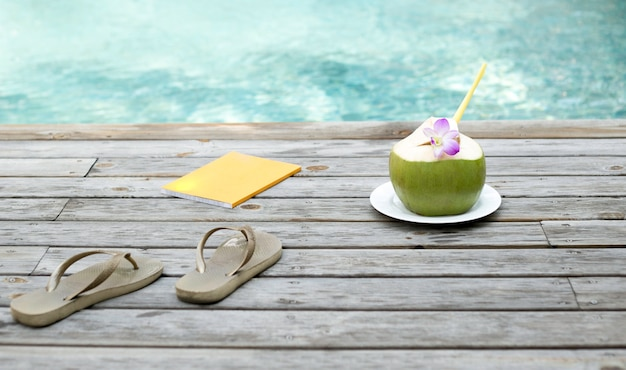 Coconut juice  with flower and book by the swimming Premium Photo