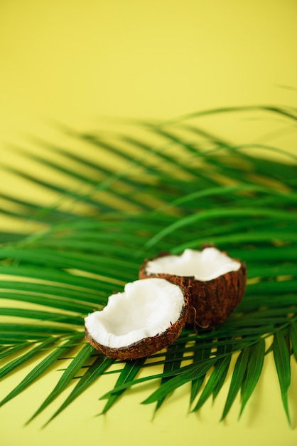 Coconut over tropical green palm leaves on yellow background. pop art design, creative summer concept. raw vegan food. Premium Photo
