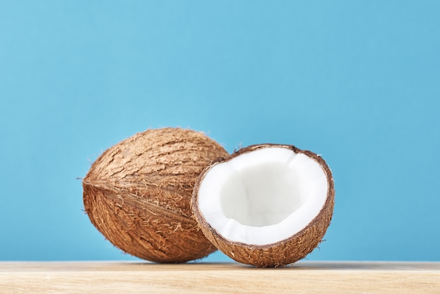 Coconut with half on wooden table against blue background Premium Photo