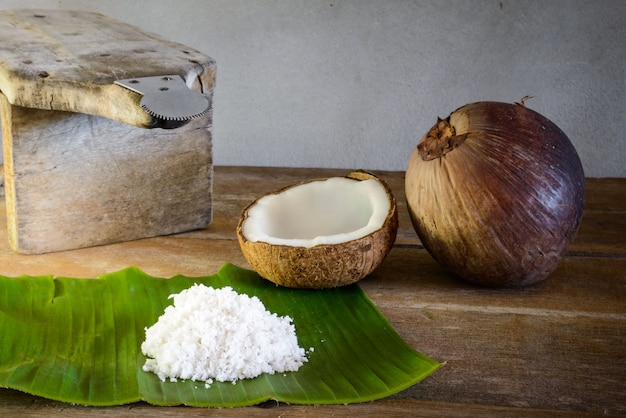 Coconuts and coconut flakes on banana leaf and coconut grater Premium Photo