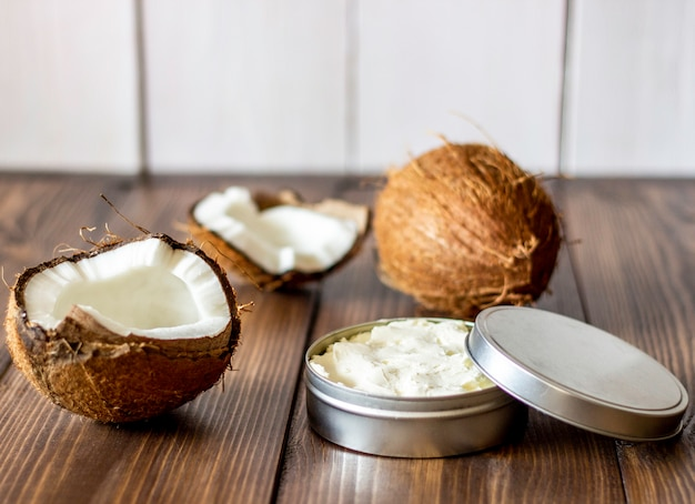 Coconuts and coconut oil in a metal pot. wooden background. Premium Photo