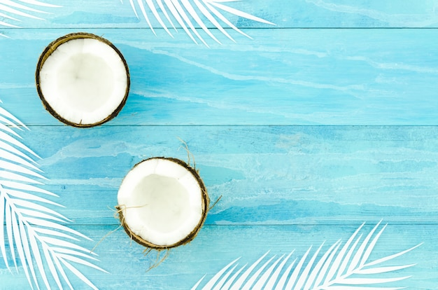 Coconuts with palm leaves on wooden table Free Photo