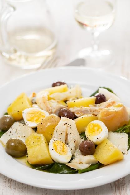 Треска с овощами и вареным яйцом на блюде Premium Фотографии