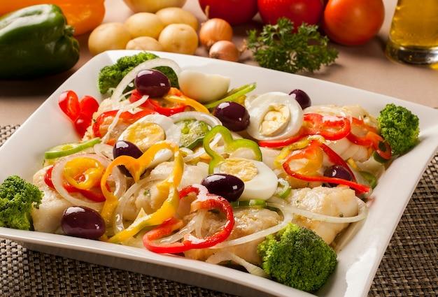 Треска - рыбное филе в соусе и овощах на столе. Premium Фотографии