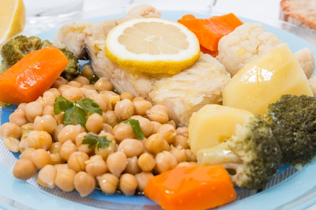Codfish with chickpeas and vegetables Premium Photo