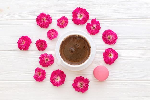 白い木製の背景にコーヒーカップのバラとピンクのマカロン Premium写真