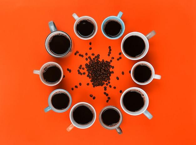 Кофе и бобы в разных чашках на ярко-оранжевом фоне Premium Фотографии