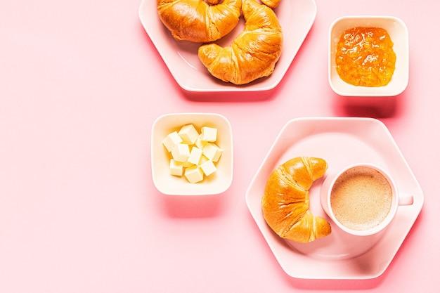 Кофе и круассаны на завтрак на розовом фоне, вид сверху, плоская планировка. Premium Фотографии