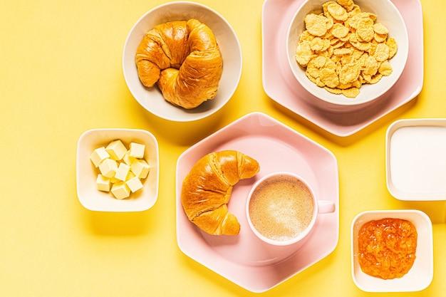 Кофе и круассаны на завтрак на желтом фоне, вид сверху, плоская планировка. Premium Фотографии