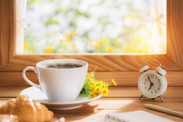 朝日が差し込む窓際に置いた朝食用のコーヒーと花 Premium写真
