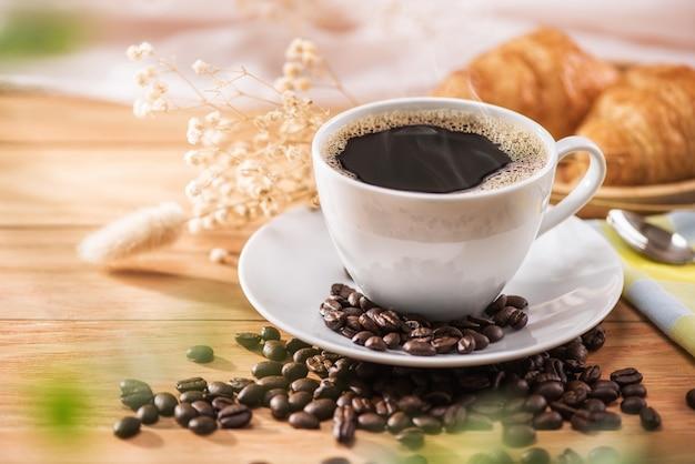 朝の陽光と朝食のためのコーヒーと花 Premium写真