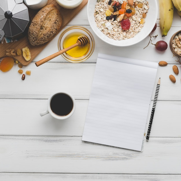 Coffee and notebook near breakfast food Free Photo