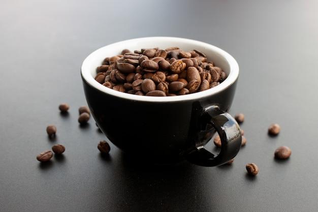 黒の背景の上にカップのコーヒー豆 Premium写真