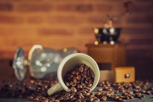 木製のテーブルに白いカップとコーヒーグラインダーでコーヒー豆。朝の朝食またはコーヒータイム。 Premium写真