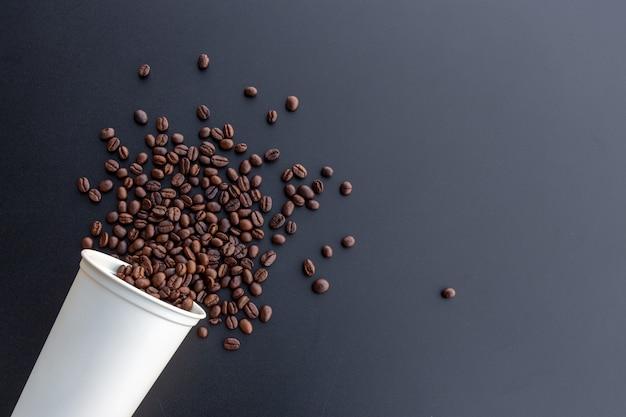 机の背景に白のホットカップのコーヒー豆 Premium写真