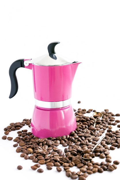 Coffee bean, pink coffee pot and spoons on white background Premium Photo