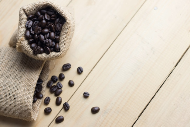 Coffee bean in sack on wooden table. high angle view Premium Photo