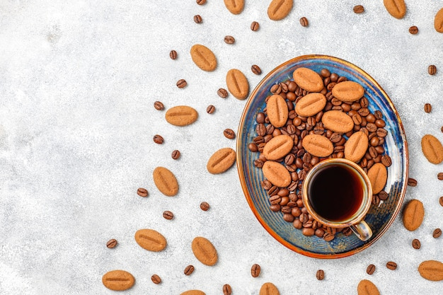 Coffee bean shaped cookies and coffee beans. Free Photo