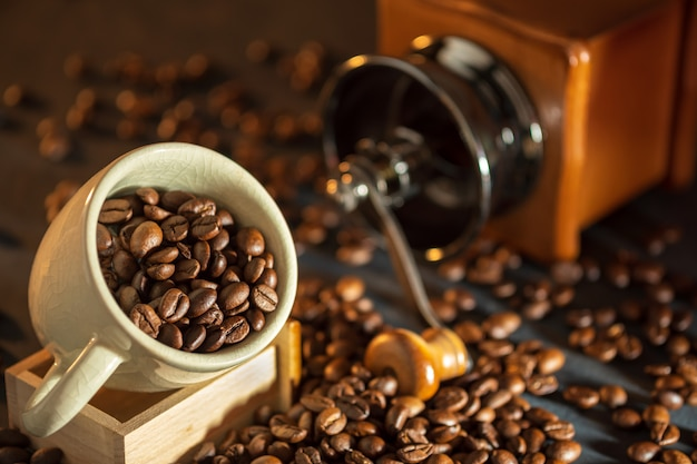 Coffee bean in the white cup and coffee grinder on wooden table. concept breakfast or coffee time in morning. Premium Photo