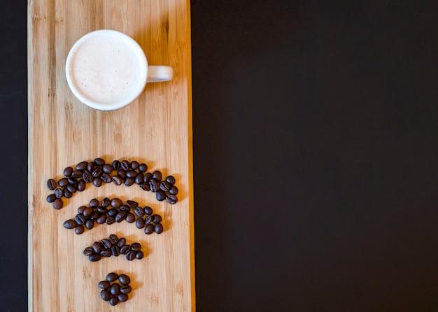 Символ wifi кофейного зерна с кружкой на деревянной доске Бесплатные Фотографии