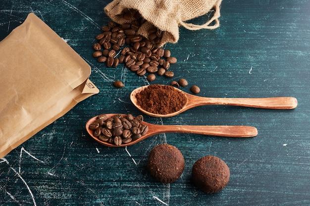 木のスプーンでコーヒー豆と粉末。 無料写真