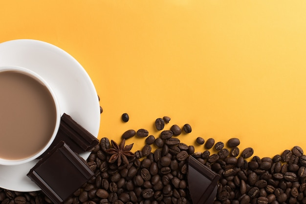 Coffee beans are scattered on a yellow paper  and a white cup, chocolate, , commercial copyspace. Premium Photo