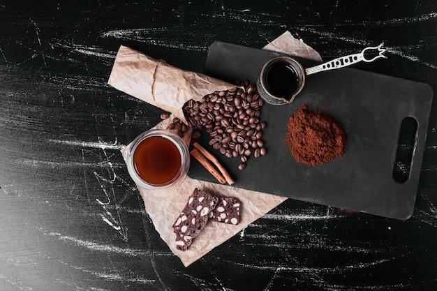 Chicchi di caffè su sfondo nero con polvere. Foto Gratuite