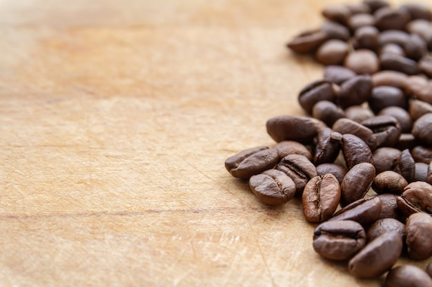 Coffee beans on brown grunge wooden background. closeup, selective focus, copyspace Premium Photo