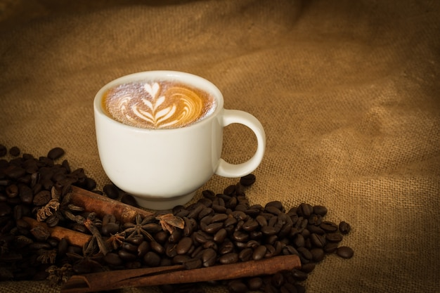 Coffee beans and cup coffee on the cloth sack select focus, vintage color tone or dark tone Premium Photo