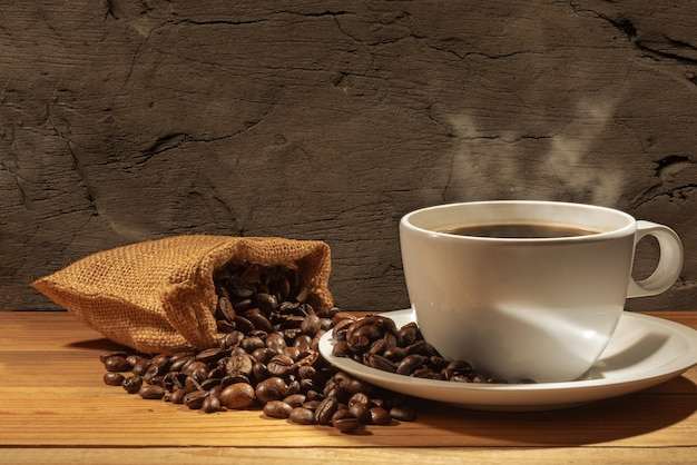 Coffee beans and a cup of hot coffee on brown wall Premium Photo