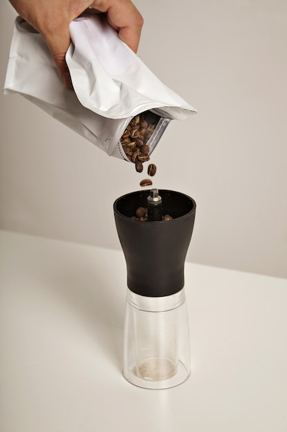 Coffee beans fall into a compact slim manual grinder standing on white table from a white foiled bag Free Photo