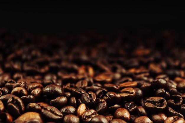 Плоские кофейные зерна лежали на деревянном столе на черном фоне. низкий ключ. скопируйте пространство. Premium Фотографии