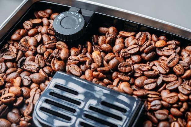 Coffee beans grinding in a coffee machine grinder Premium Photo