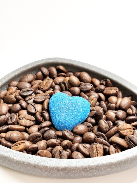 白のボウルとマーマレードの心のコーヒー豆。 Premium写真
