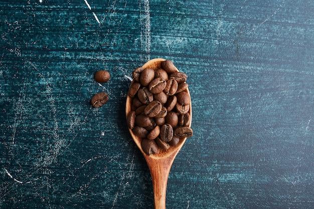 木のスプーンでコーヒー豆。 無料写真
