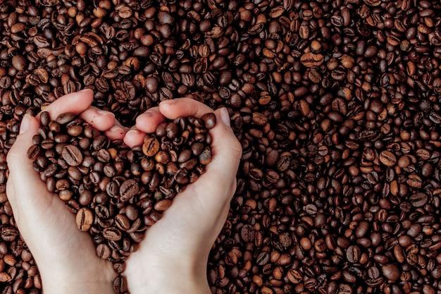 コーヒーのハートの形で男の手のひらのコーヒー豆。 Premium写真