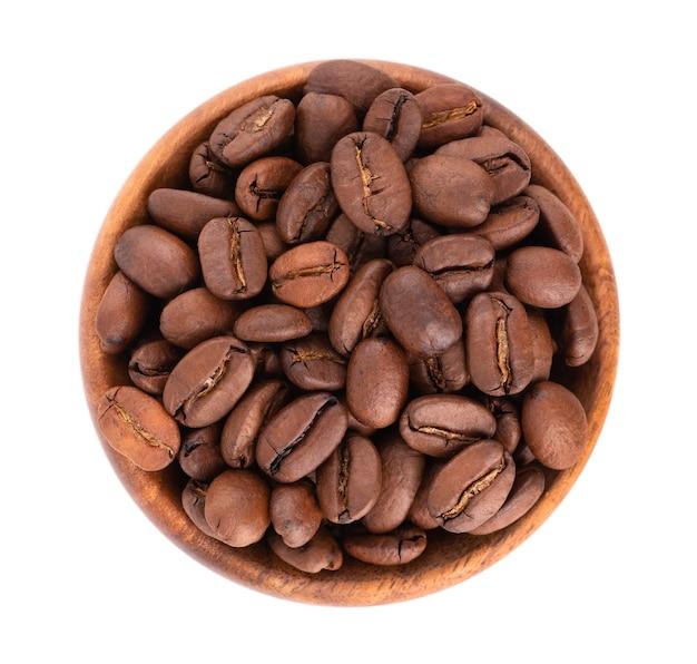 白い背景で隔離の木製ボウルのコーヒー豆。アラビカコーヒー豆の焙煎。上面図。 Premium写真