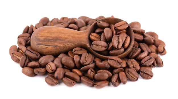 白い背景で隔離のコーヒー豆。木のスプーンで焼いたアラビカコーヒー豆。 Premium写真