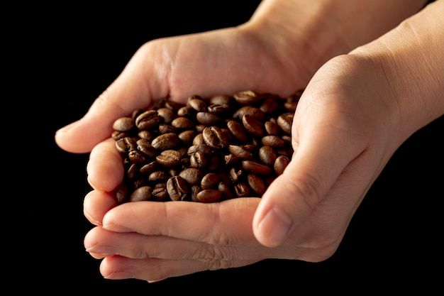 Coffee beans in a mans hands Free Photo