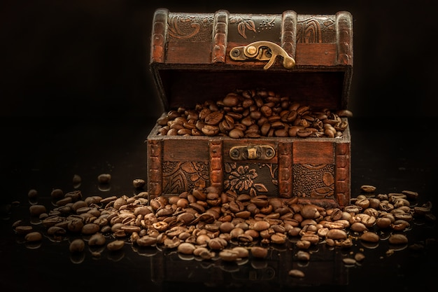 Coffee beans and old treasure chest on black background - the black gold Premium Photo