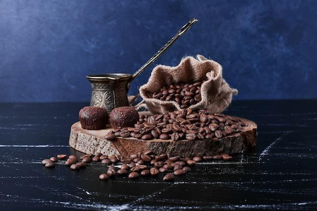 素朴な小包の黒い背景にコーヒー豆。 無料写真
