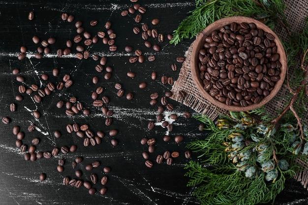 木製のカップの黒い背景の上のコーヒー豆。 無料写真