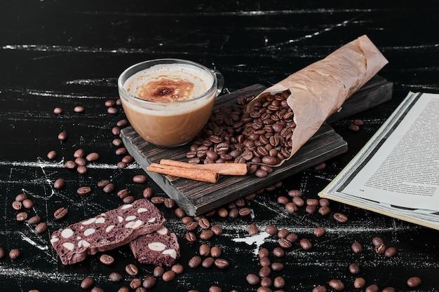 음료와 쿠키와 검은 배경에 커피 콩. 무료 사진
