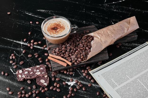 飲み物とクッキーと黒の背景にコーヒー豆。 無料写真