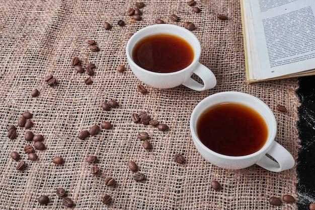 삼 베에 음료와 함께 검은 배경에 커피 콩. 무료 사진